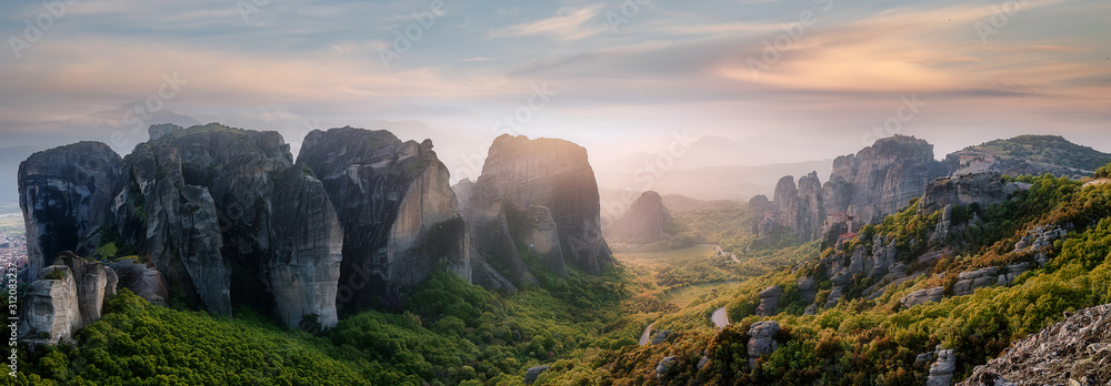 Fototapeta Wonderful Panoramic view of Meteora. Majestic sunny landscape with colorful sky over the fairytale mountain valley in Greece. Amazing spring scene of Famouse Kalabaka location, Greece, Europe
