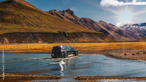 Photo car fords  through river in iceland