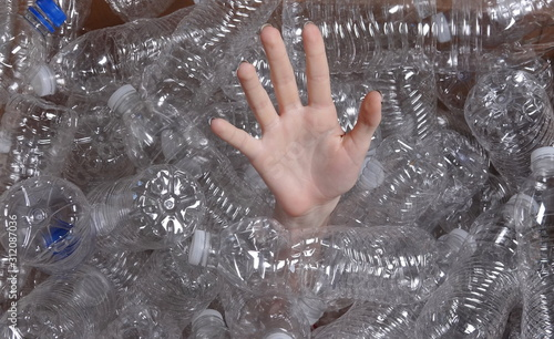 Photo A teen's hand reaching from pile of plastic bottles