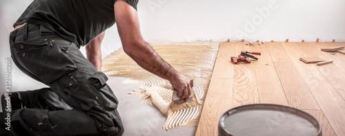 Obraz Handwerker verlegt Parkettboden und streicht den Estrich mit Kleber ein und schlägt die Dielen mit dem Hammer und dem Schlagklotz zusammen - fototapety do salonu