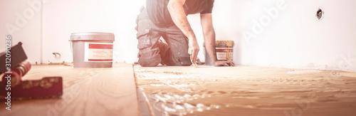 Fotomural Handwerker verlegt Parkettboden und streicht den Estrich mit Kleber ein und schl