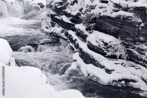 Rapids in a chute of Hogs Back Falls in Ottawa Canada after a snow storm