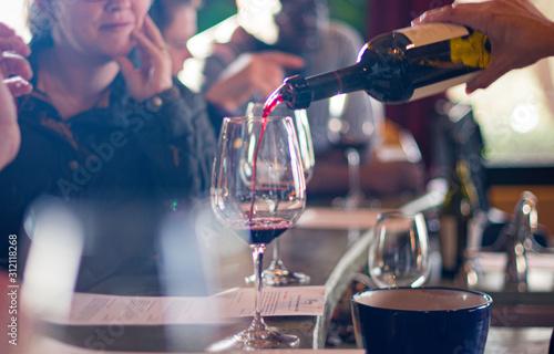 Fototapeta close up of hand pouring wine into wine glasses at wine tasting obraz