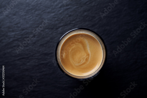 Photo Coffee in glass cup on dark stone background