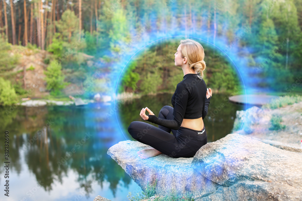 Fotografia Beautiful young woman meditating near lake