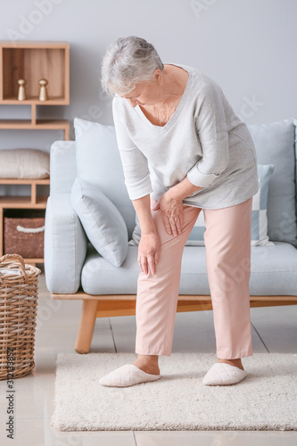 Cuadros en Lienzo Senior woman suffering from pain in knee at home