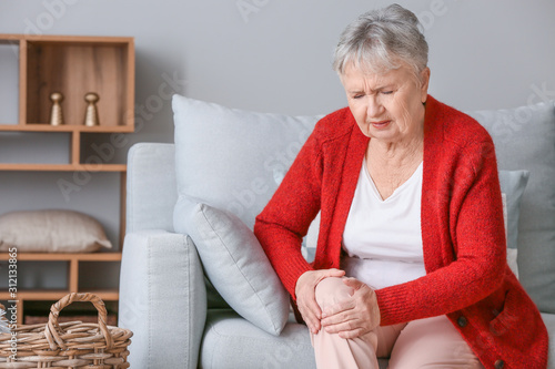 Fotomural Senior woman suffering from pain in knee at home