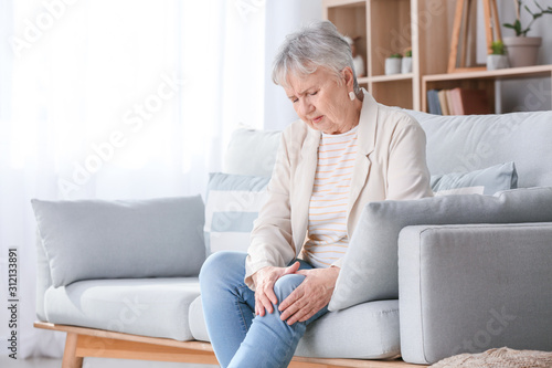 Fotografía Senior woman suffering from pain in knee at home