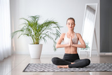 Beautiful Young Woman Practicing Yoga At Home