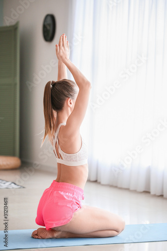 Photo Beautiful young woman practicing yoga at home