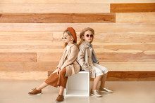 Cute Little Girls In Autumn Clothes Near Wooden Wall