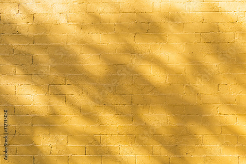 Shadow and light on yellow brick wall background texture