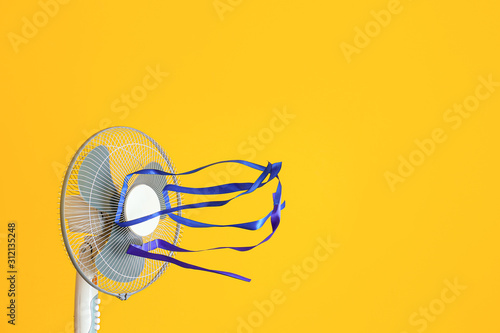 Foto Electric fan with fluttering ribbons on color background