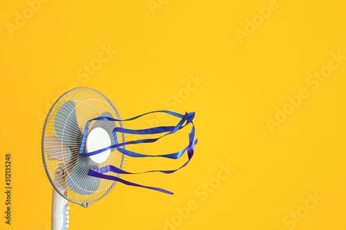 Fototapeta Electric fan with fluttering ribbons on color background obraz