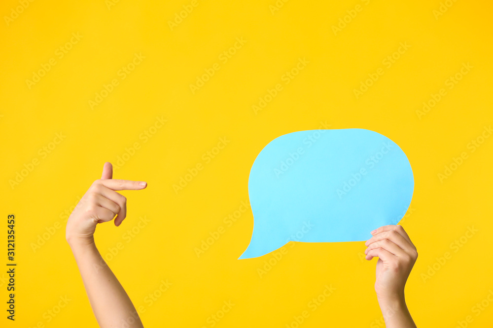 Fototapeta Female hands and blank speech bubble on color background