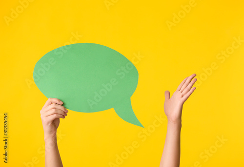 Obraz Female hands and blank speech bubble on color background - fototapety do salonu
