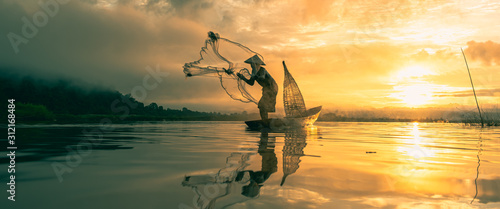 Canvastavla  Fisherman throwing fishing net during sunrise.
