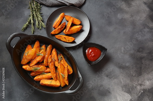 Fényképezés Baked, fried potato wedges with spices and rosemary