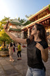 Tourist girl taking a selfie in the front of buddhist temple on a popular travel destination in Vietnam