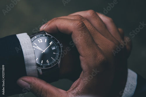 Fototapeta looking at luxury watch on hand check the time at workplace.concept for managing time organization working,punctuality,appointment.fashionable wearing stylish obraz