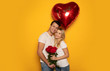 Love is in the air. Close-up photo of an attractive couple, who are hugging and holding a red heart-shaped balloon and a bouquet of roses in their hands while smiling at the camera.