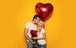Perfect love. Сlose-up photo of a charming lady and her handsome boyfriend, who is kissing her in the cheek, while giving her a bouquet of roses and a big red heart-shaped balloon.