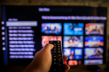 Video On Demand Screen With Remote Control In Hand