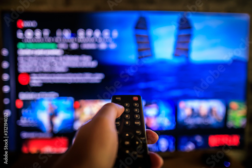 Obraz Video on demand screen with remote control in hand - fototapety do salonu