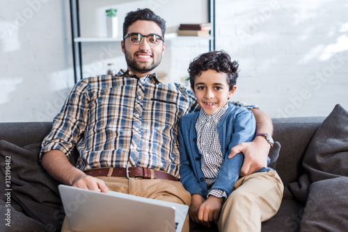 smiling jewish father with laptop and son looking at camera in apartment Wallpaper Mural
