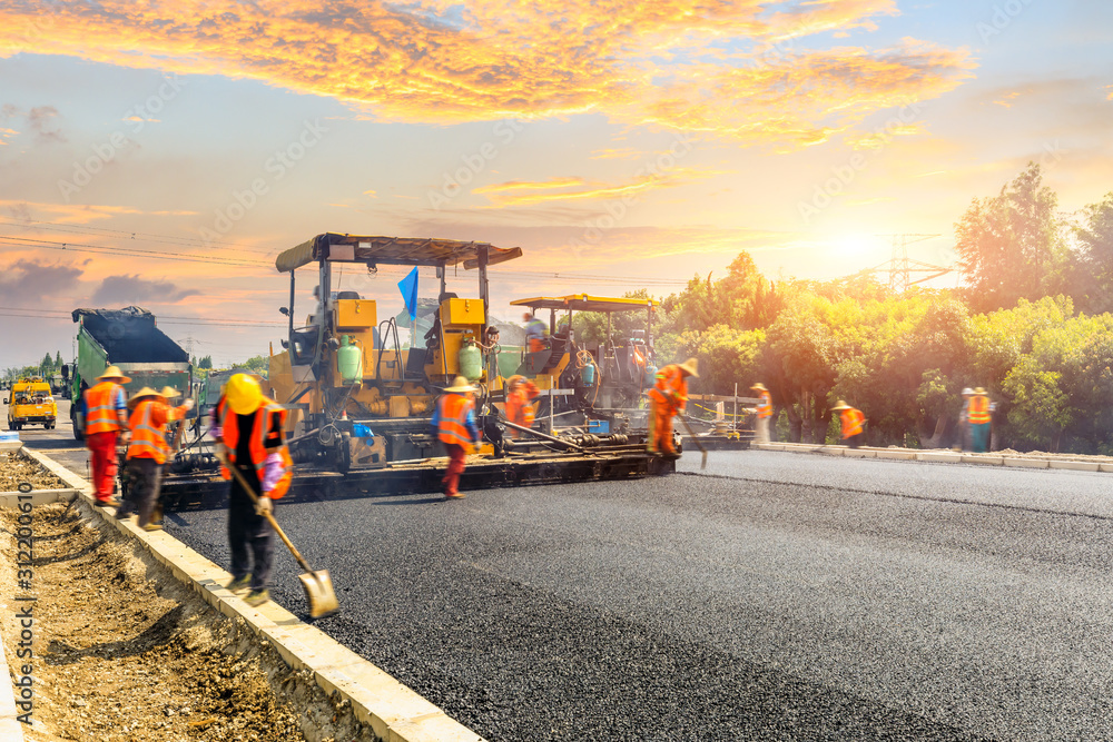 Fototapeta Construction site is laying new asphalt road pavement,road construction workers and road construction machinery scene.