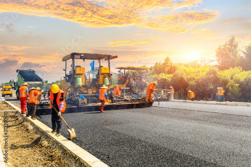 Fotografia  Construction site is laying new asphalt road pavement,road construction workers and road construction machinery scene