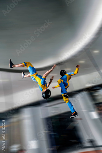 Fototapety, obrazy: Landing. Free people prefere active sports. Bird men conquers sky. Flying people in blue and yellow suit. Extreme as a hobby.