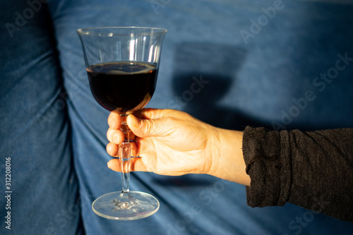 Hand catching a glass of red wine under sunlight. Canvas Print