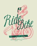 Fototapeta Dinusie - T-rex riding bicycle. Dinosaur in shades on bike typography print.