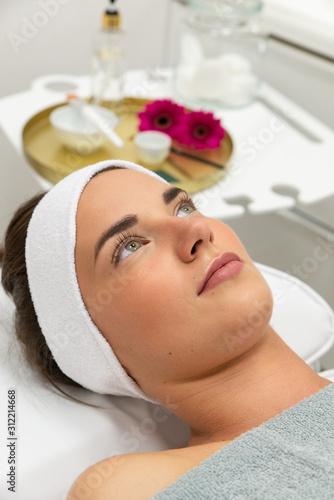Obraz Kobieta, brunetka w salonie piękności leży na fotelu kosmetycznym. - fototapety do salonu