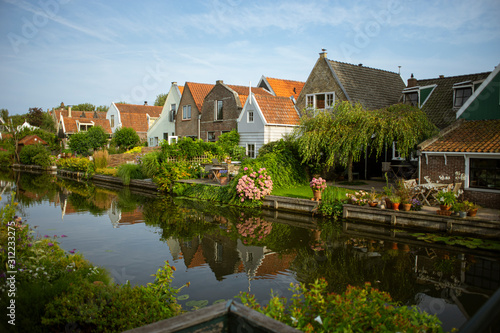 Obraz Beautiful and picturesque landscape of the village of Edam, the Netherlands. Typical dutch houses in front of a canal, riverside with trees and flowers. A sunny day. - fototapety do salonu