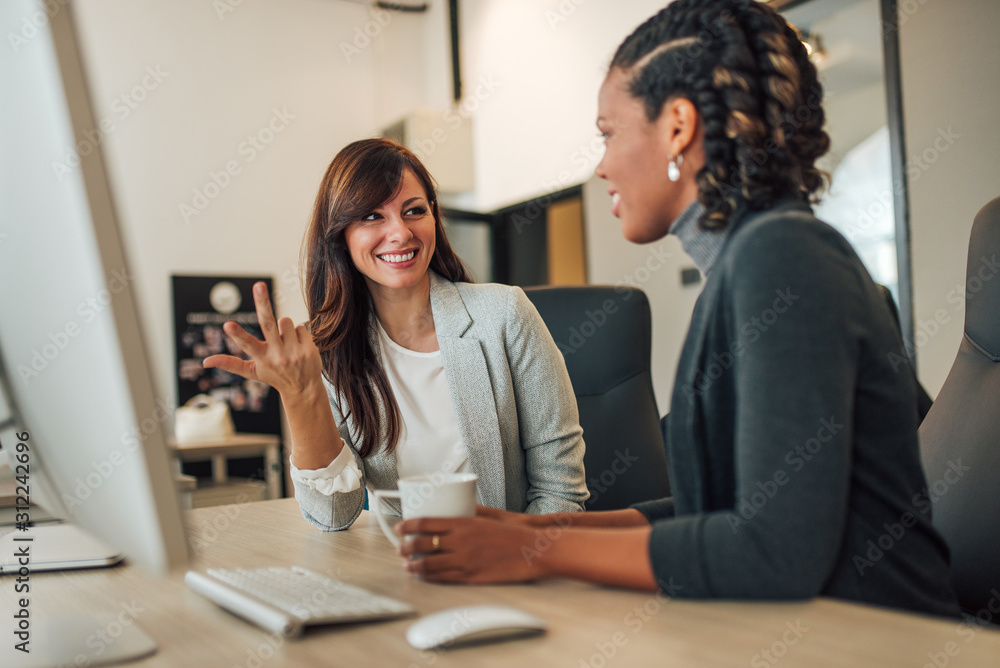 Fototapeta Portrait of a two businesswomen talking while working together at modern workplace.