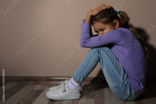 Fotomural Scared little girl near beige wall, space for text