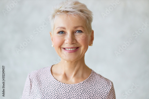 Obraz Close up image of good looking beautiful mature blonde female with blue eyes, elegant make upand pixie hairstyle smiling at camera, having confident happy facial expression, being in good mood - fototapety do salonu