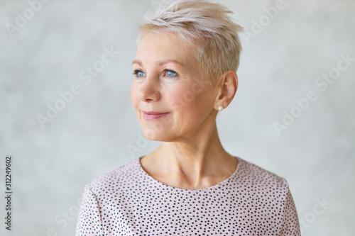 Obraz Close up studio image of beautiful attractive middle aged European lady with stylish haircut and neat make up looking away with confident smile posing isolated against marbled wall background - fototapety do salonu