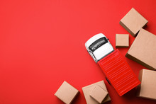 Top View Of Toy Truck With Boxes On Red Background. Logistics And Wholesale Concept