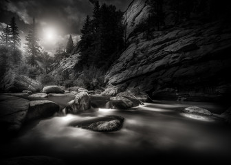Black and white scene of a mountain river in the Rocky Mountains of Colorado. This is a long exposure so the river is smooth and silky looking.