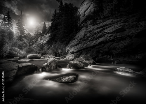 Fototapeta Black and white scene of a mountain river in the Rocky Mountains of Colorado. This is a long exposure so the river is smooth and silky looking.  obraz