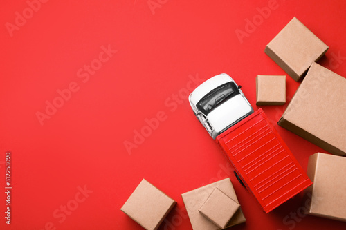 Top view of toy truck with boxes on red background Fototapeta