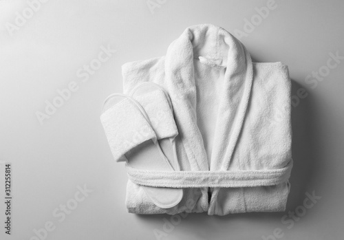 Canvastavla Clean folded bathrobe and slippers on white background, top view