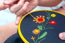 Women's Hand Embroidery In A Hoop, A Woman Embroider A Pattern On Dark Material. Close-up. The Concept Of Needlework, Hobby, Leisure.