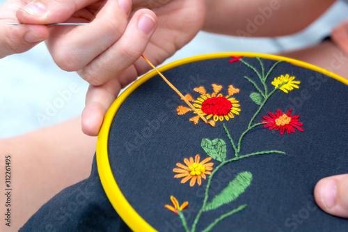 Women's hand embroidery in a hoop, a woman embroider a pattern on dark material Canvas Print