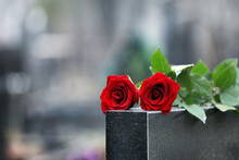 Red Roses On Black Granite Tombstone Outdoors. Funeral Ceremony