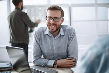close up. smiling businessman sitting at his Desk