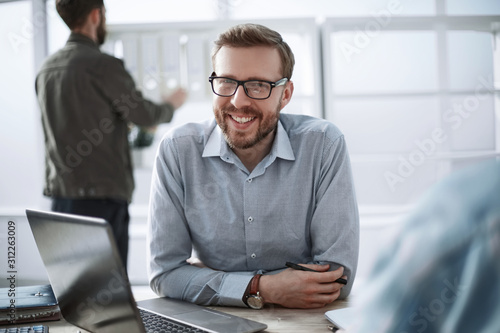 Obraz close up. smiling businessman sitting at his Desk - fototapety do salonu